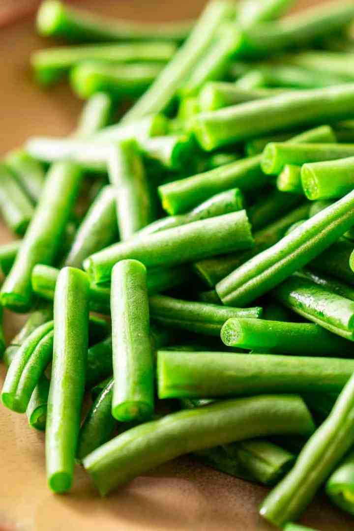 A pile of trimmed and cut fresh green beans on a wooden board.