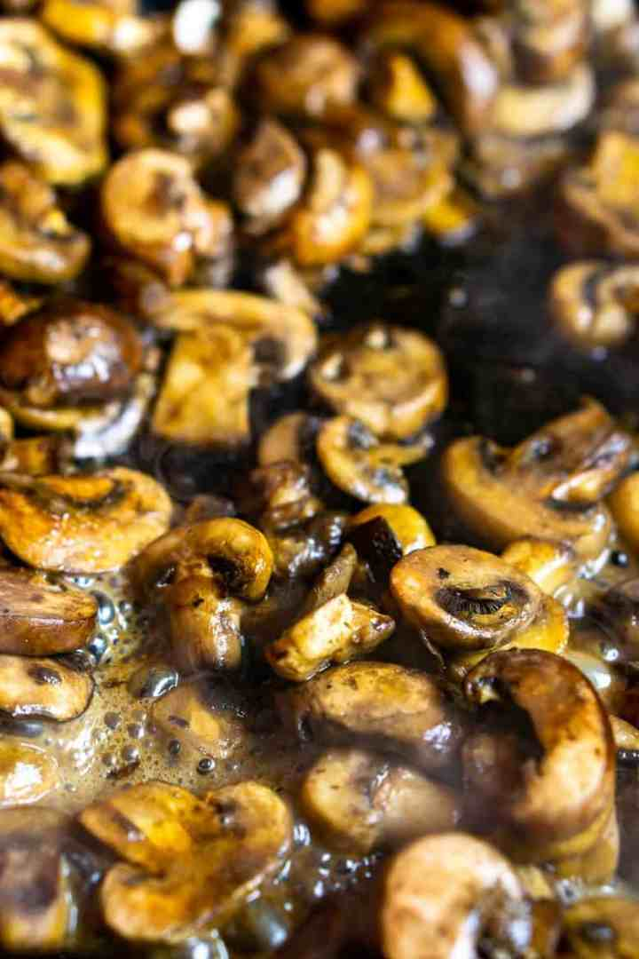 The sliced mushrooms after they've reduced in a cast-iron skillet.