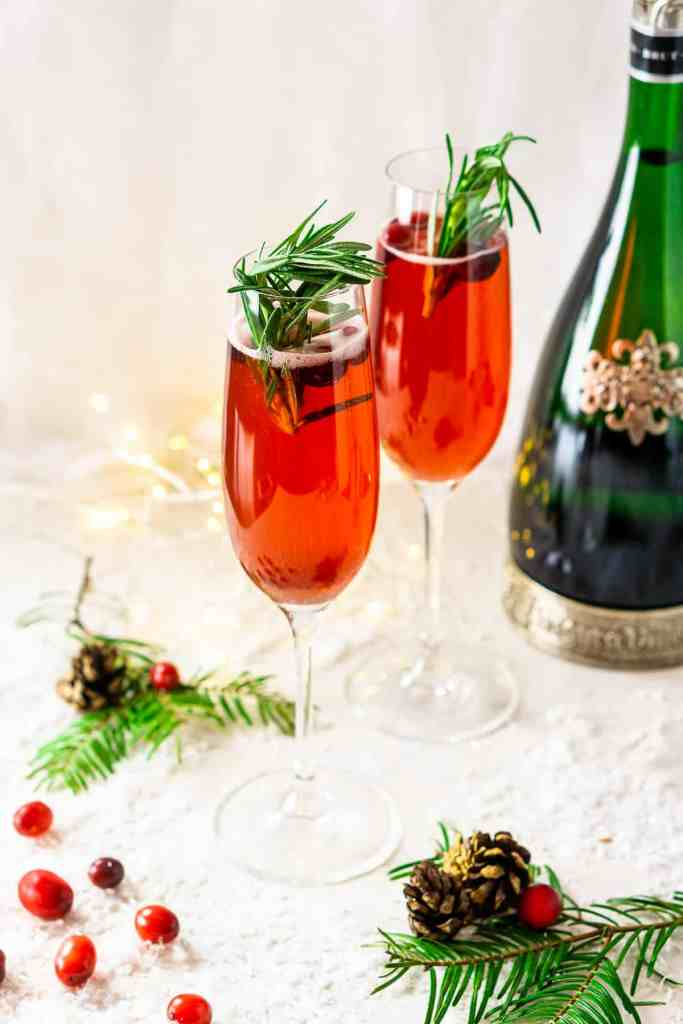 Two Christmas mimosas with pine leaves and fresh cranberries and fake snow.