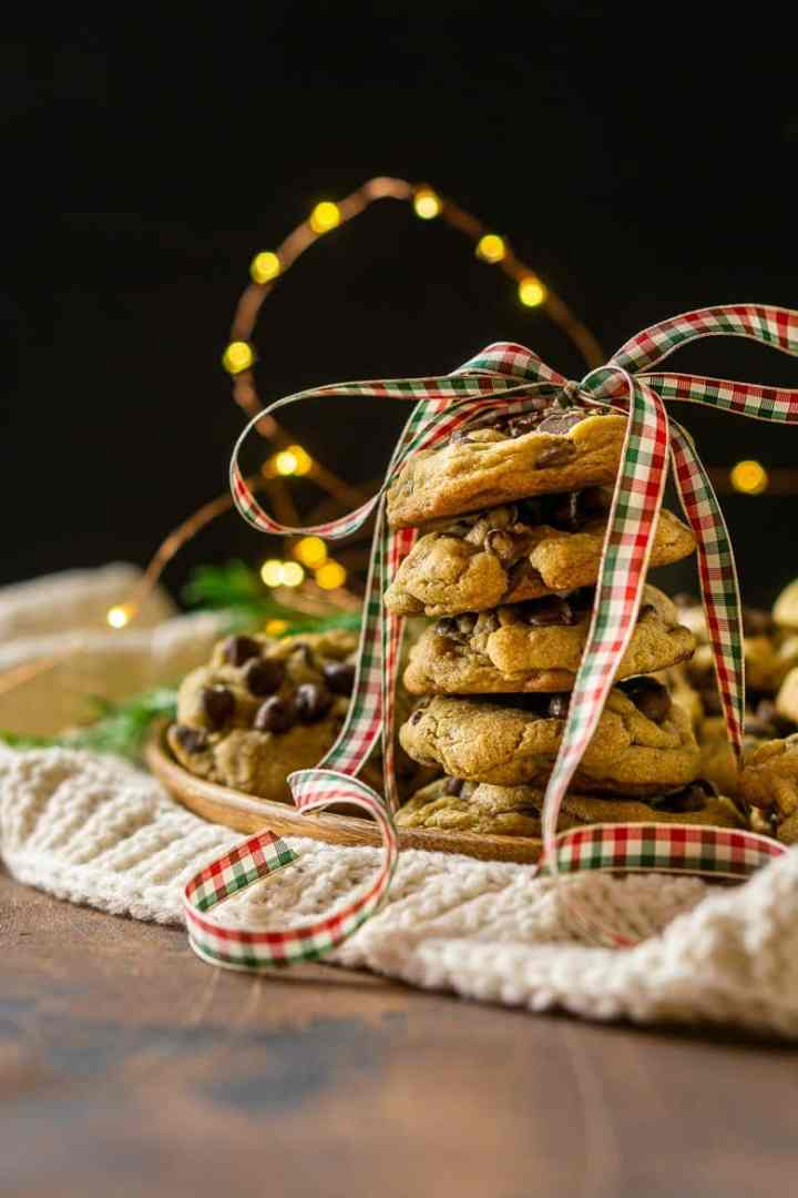 Looking straight on to a stack of spiced holiday chocolate chip cookies with a Christmas.