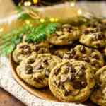 A plate of spiced holiday chocolate chip cookies on a wooden plate with pine needles and lights in the background.