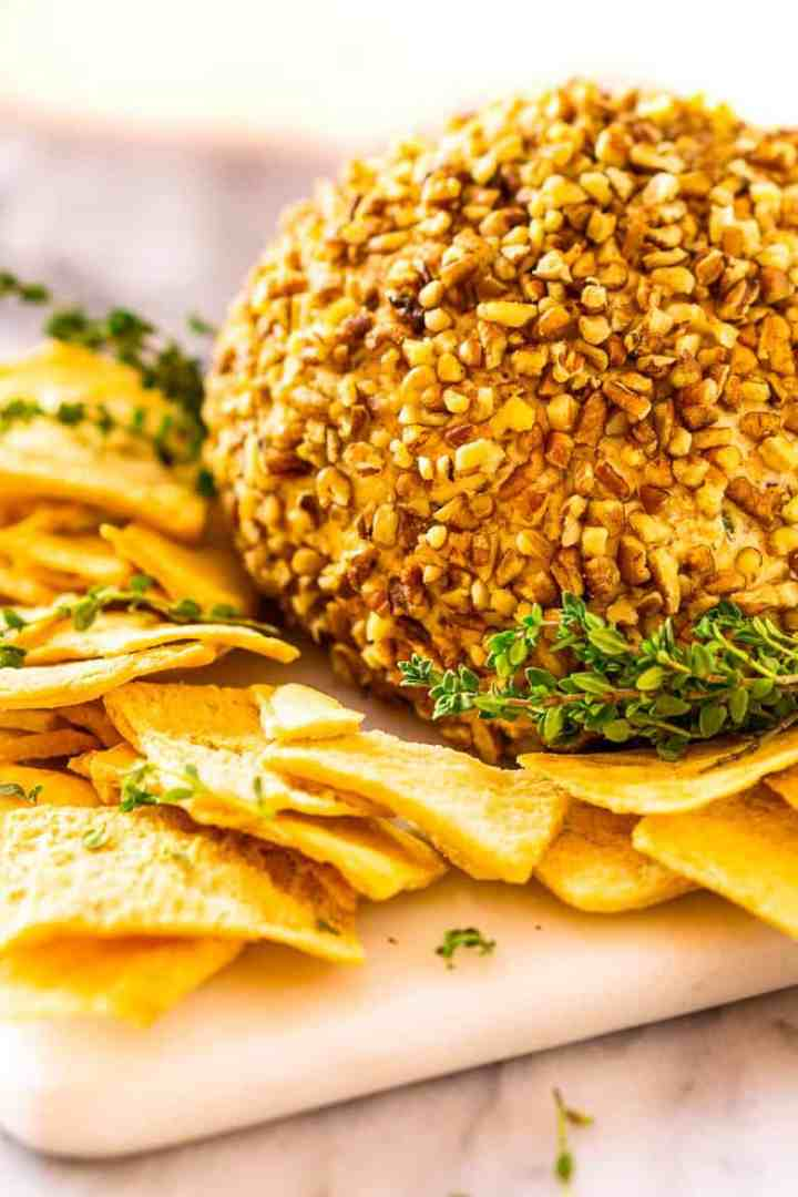 Looking down on the bourbon bacon jam cheese ball with fresh thyme and pita chips.