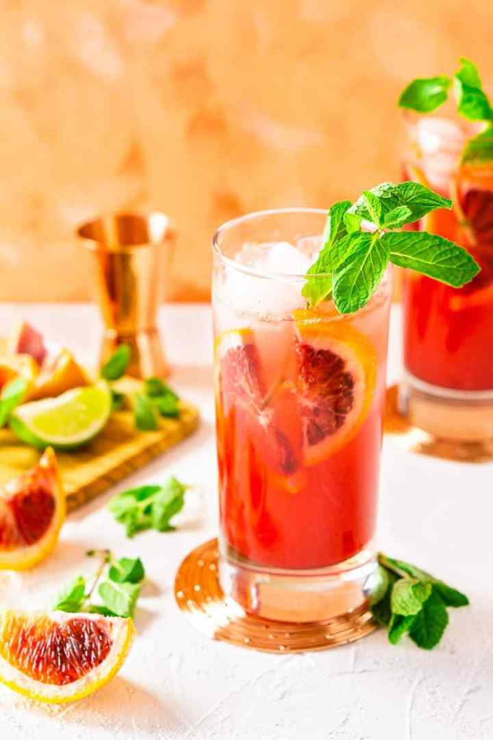 Two blood orange mojitos with fresh mint and fruit around it with a copper jigger.