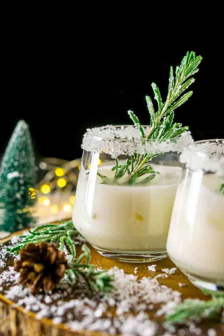 A closer shot of a winter margarita with candied rosemary and fake snow around it.