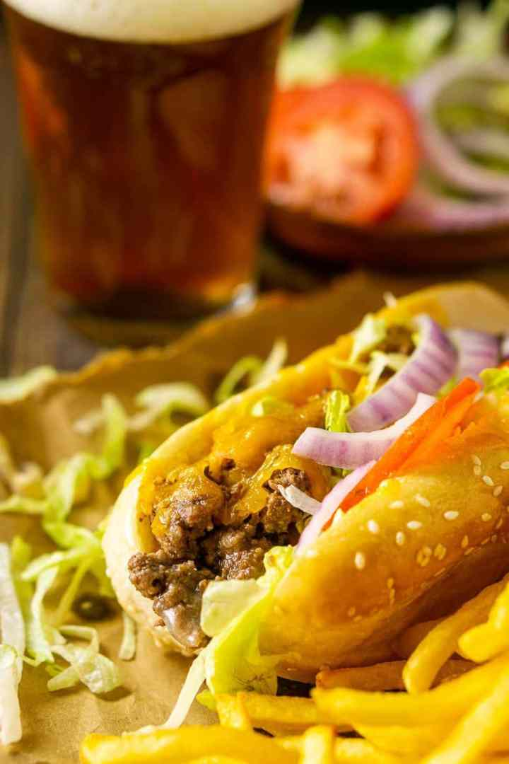 A close-up shot of the cheeseburger sub with a beer in the background.
