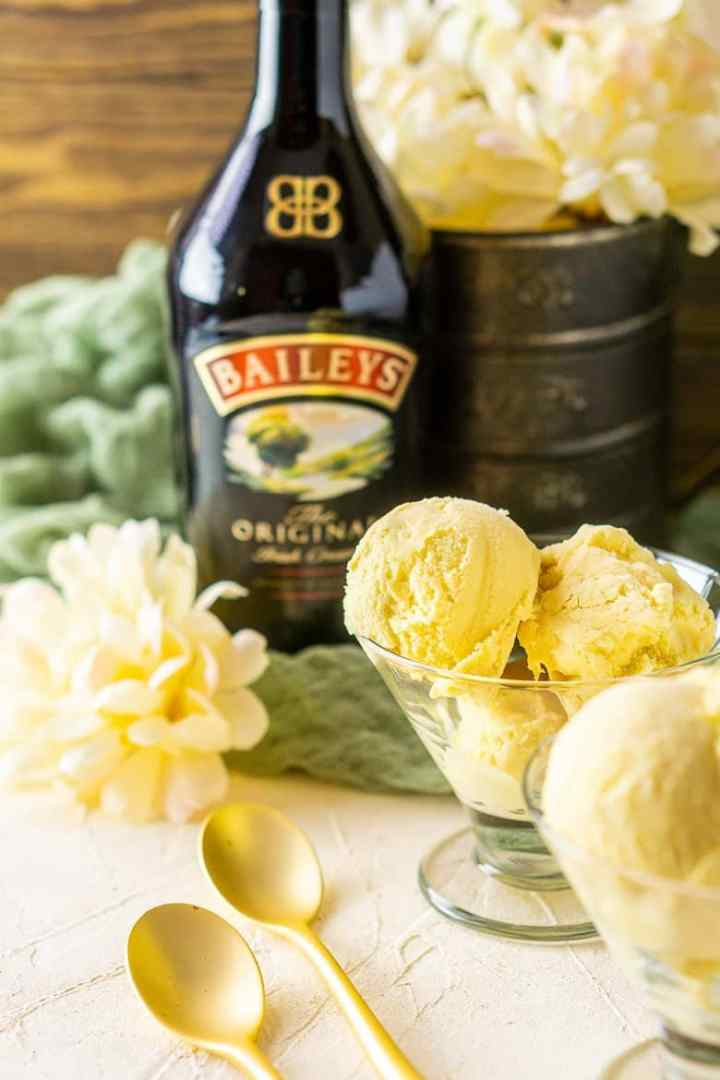 A glass cup with Baileys ice cream and flowers in the background.