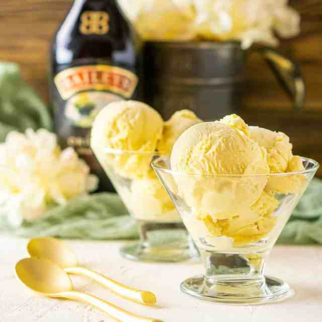 A glass cup holding a few scoops of Baileys ice cream with a bottle of Irish cream in the background.