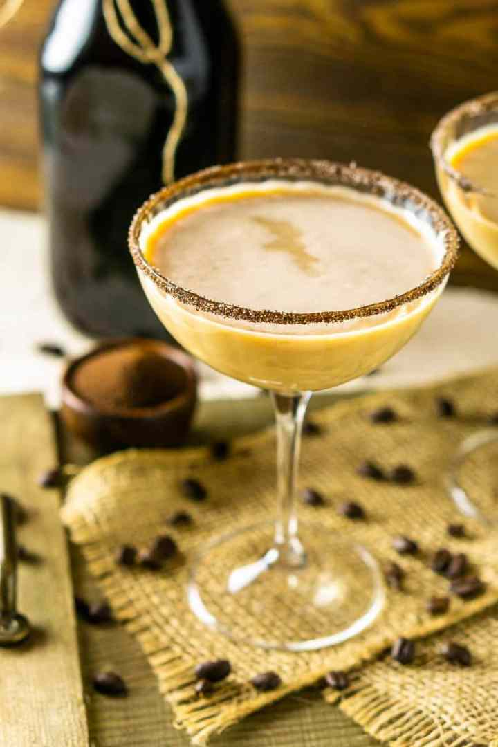 Looking down into one Baileys Irish coffee martini with a focus on the espresso-sugar rim on burlap.