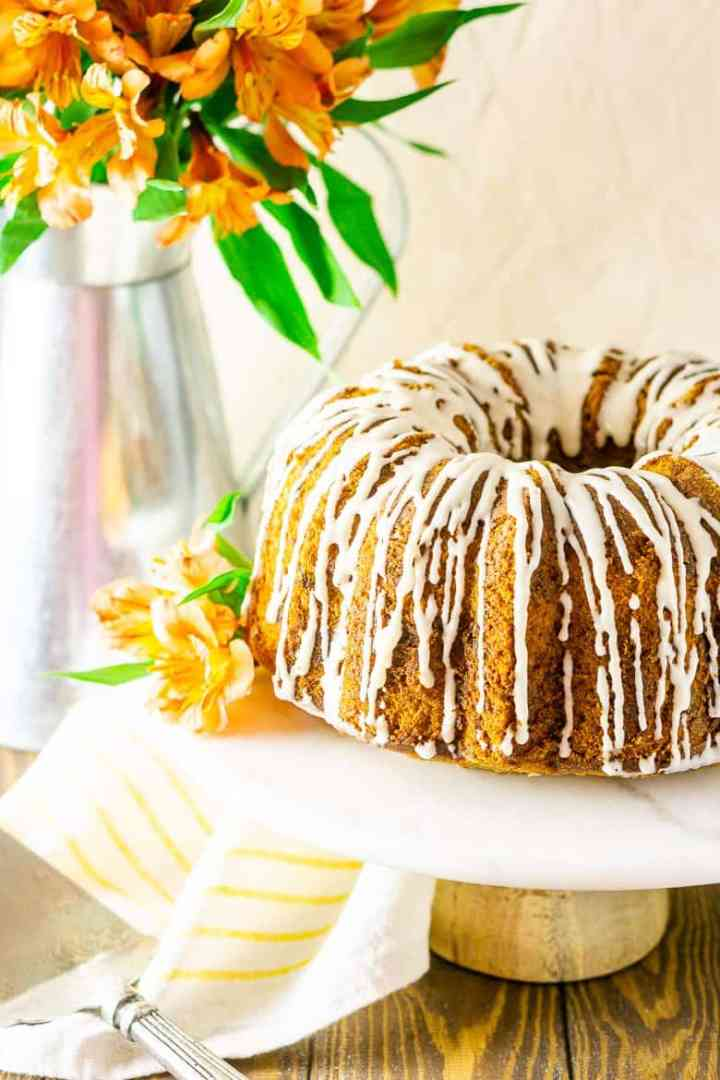 The carrot pound cake on a white marble cake stand with orange flowers.