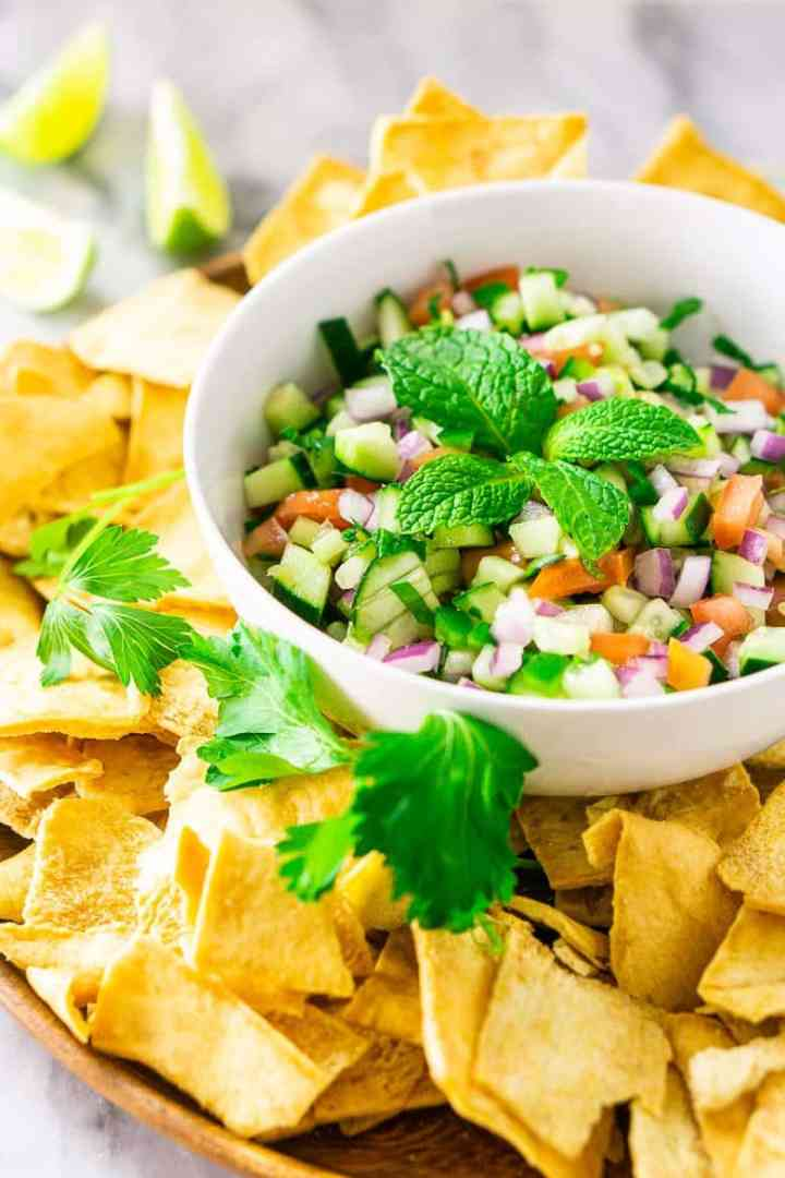 A white bowl with Mediterranean-inspired cucumber pico de gallo with pita chips and limes.