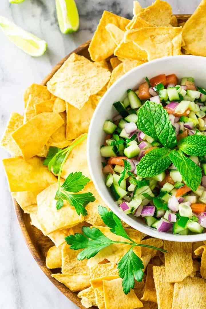 An aerial view of the cucumber pico de gallo on a wooden plate with pita chips.