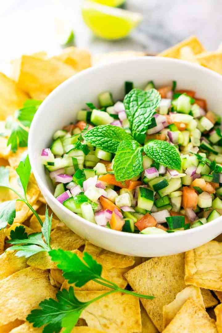 A bowl of Mediterranean cucumber salsa surrounded by pita chips and parsley.