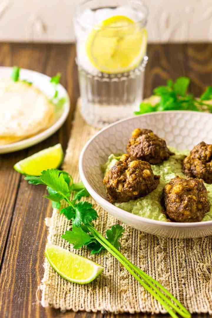 The Mexican meatballs with a lemon water on a placemat.