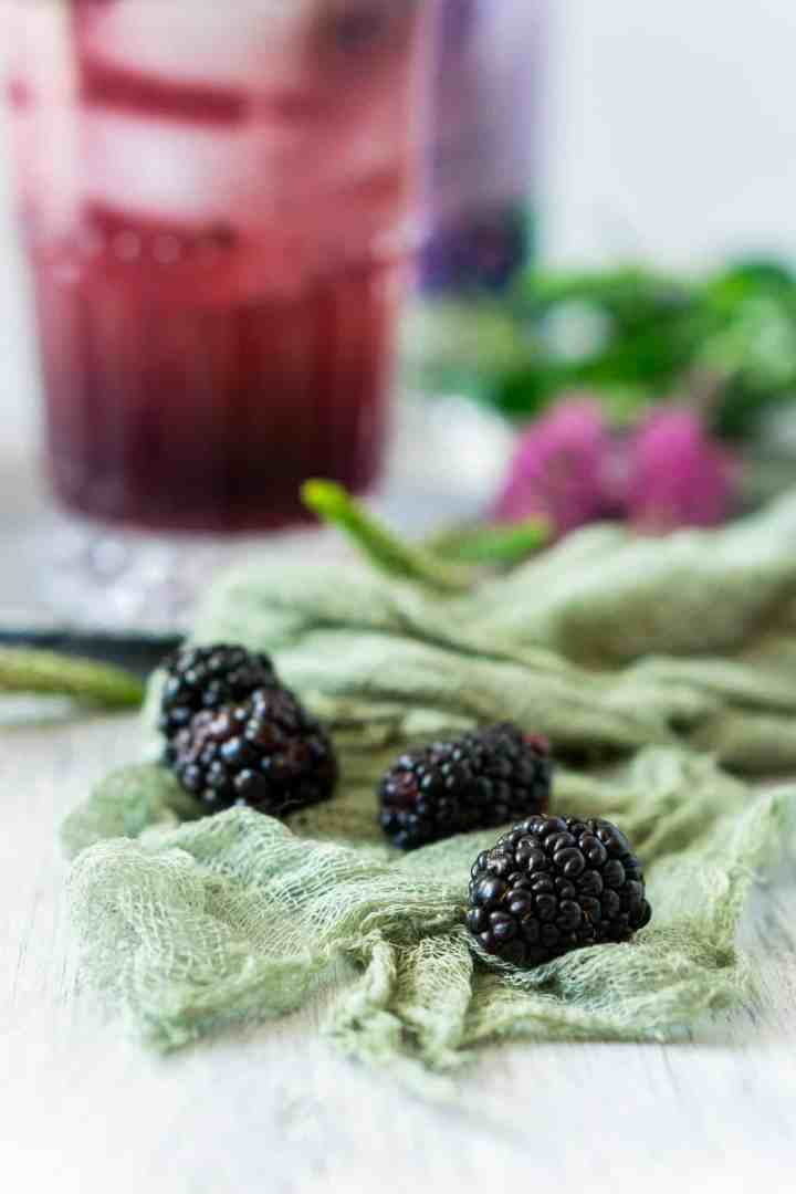 A few blackberries on green cheesecloth with purple flowers in the background.