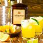 Two Italian margaritas with a bottle of amaretto in the background with fresh orange and lime slices around them.