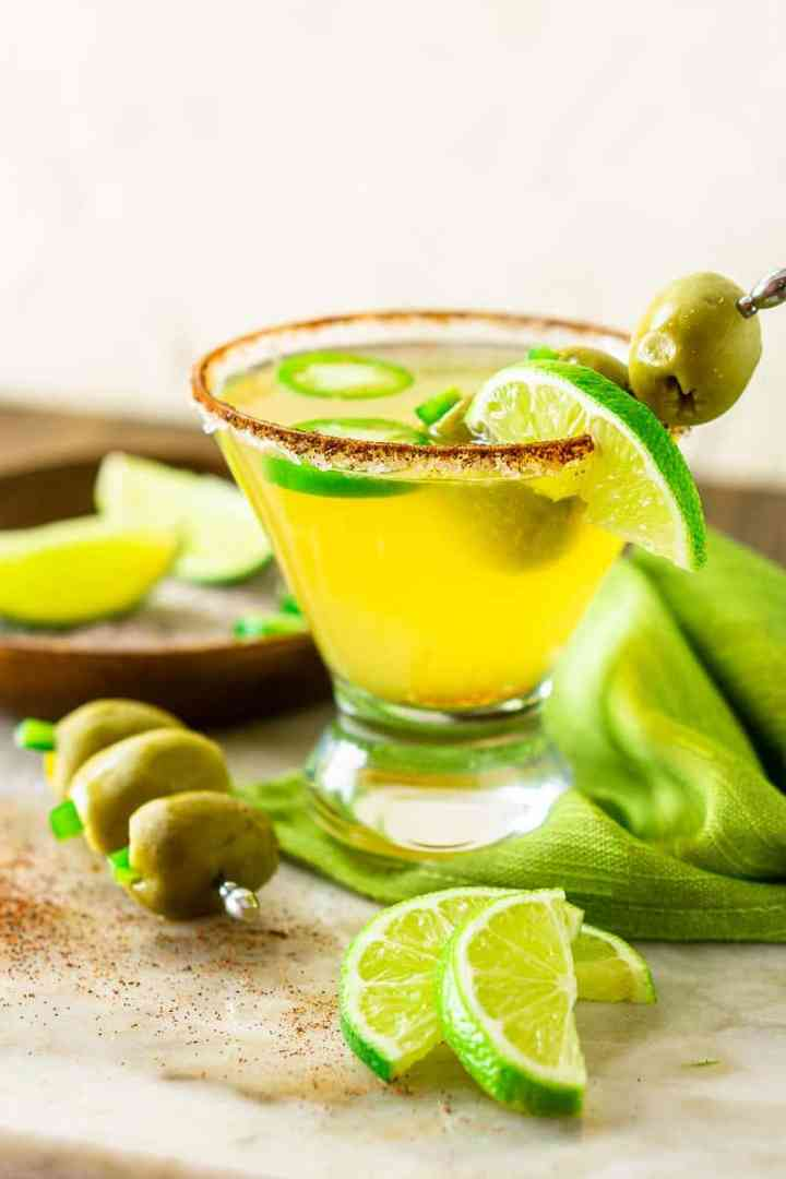 A spicy Mexican martini with lime slices and a steel toothpick with olives on it.