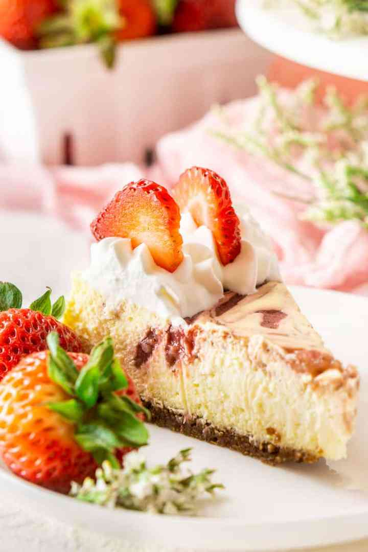 A close-up shot of a slice of fresh strawberry-ginger cheesecake on a white plate.