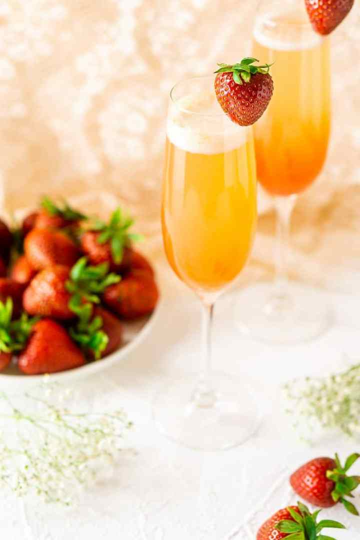 Looking down at two strawberry-rhubarb mimosas on a white background.