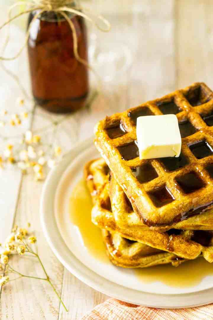 A stack of buttermilk waffles with the syrup on the side.
