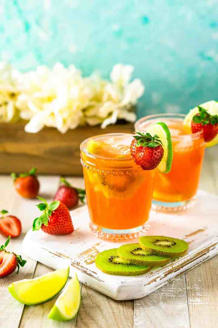 A strawberry-kiwi margarita on a white wooden board with fruit surrounding it and flowers in the background.