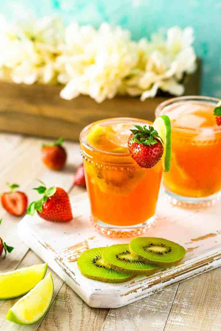 Two strawberry-kiwi margaritas on a white wooden board with white flowers.