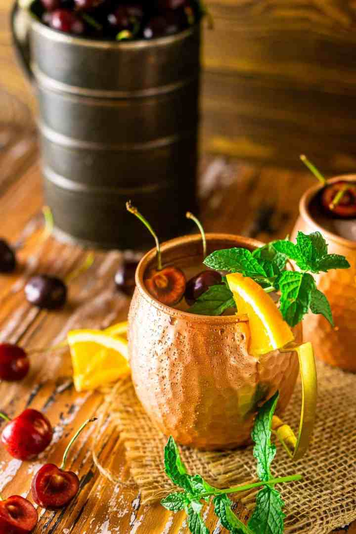 A cherry-orange Kentucky mule with a sprig of mint on burlap.