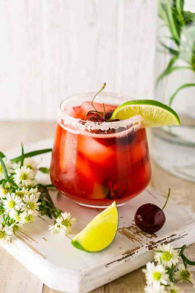 A cherry margarita with a lime slice, cherry and bundle of flowers on the side.