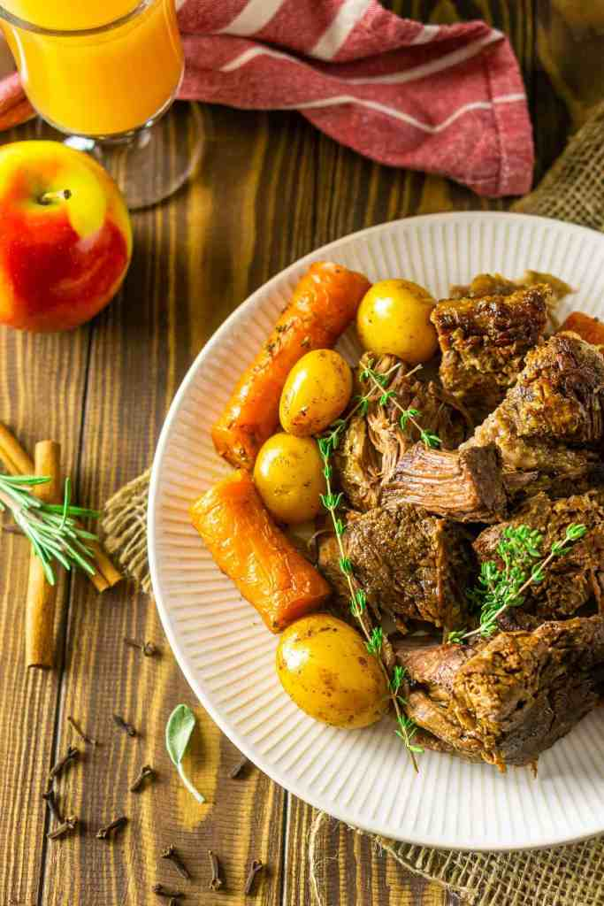 An aerial view of a plate of apple cider pot roast with a glass of apple cider and herbs and spices.