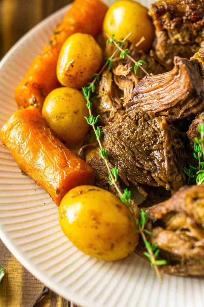 A close-up shot of the apple cider pot roast on a plate with carrots and potatoes.