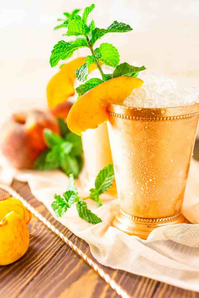 A close-up view of the brown-sugar peach mint julep with fresh peaches.