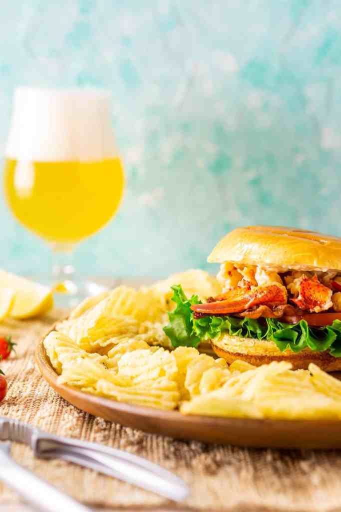 A straight-on shot of the lobster BLT with a beer in the background.