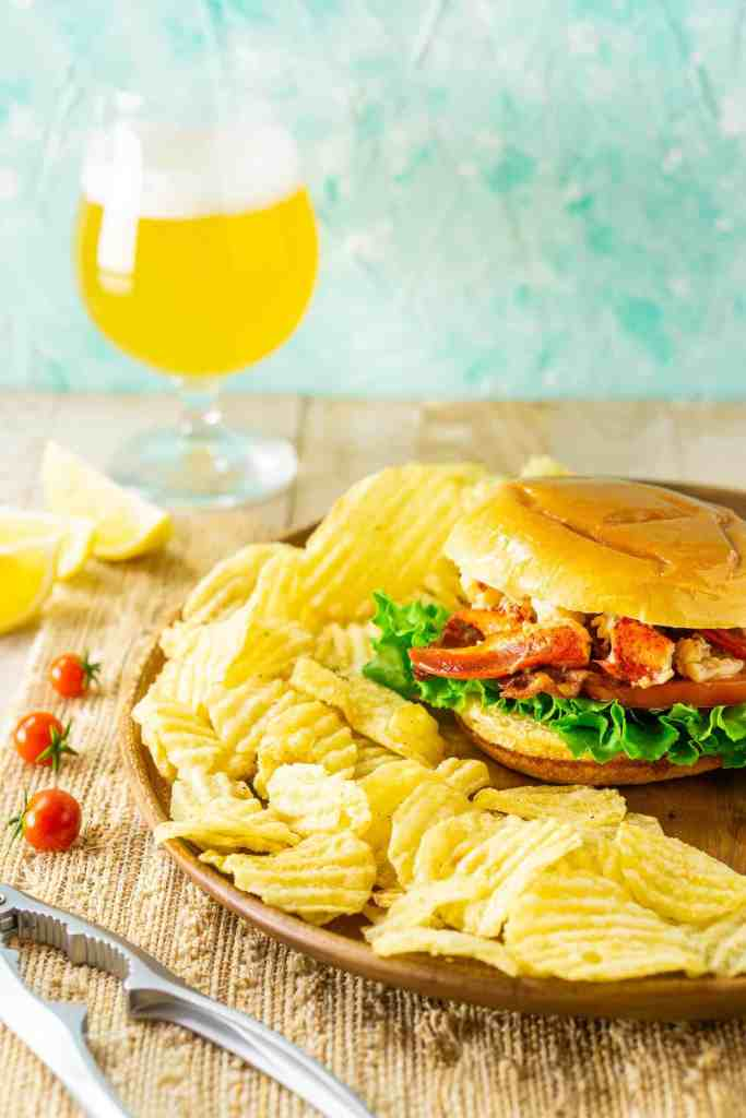 Looking down on the Connecticut-style lobster BLT on a light-colored placemat with a beer and claw cracker.
