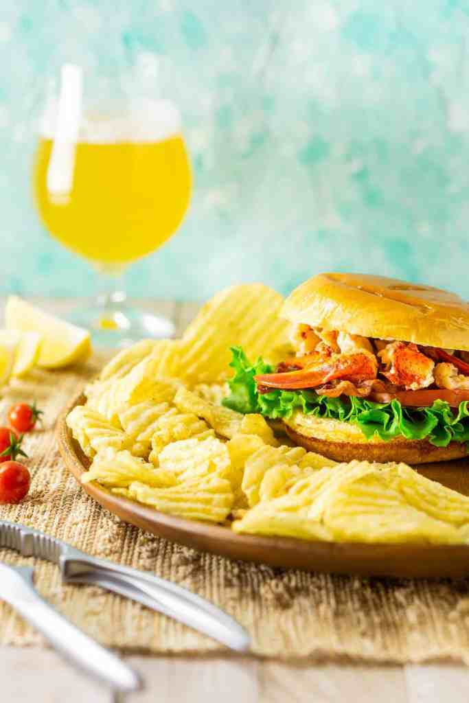 A Connecticut-style lobster BLT with chips around it, a lobster claw cracker on the side and a beer in the background.