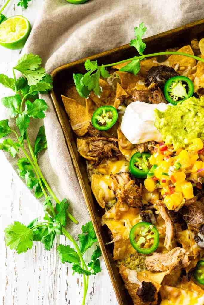 An aerial view of the sheet pan jerk pork nachos on top of a neutral-colored napkin.
