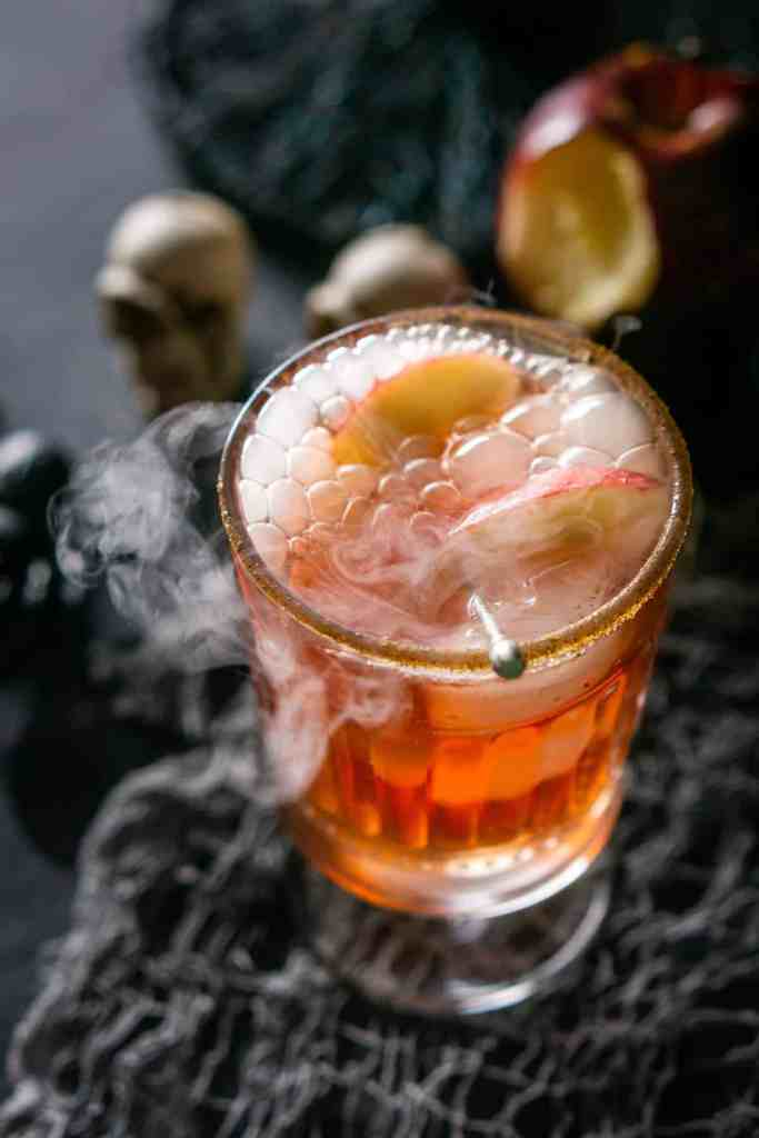 A close-up view of a single Poisoned Orchard Cocktail with skulls behind it.