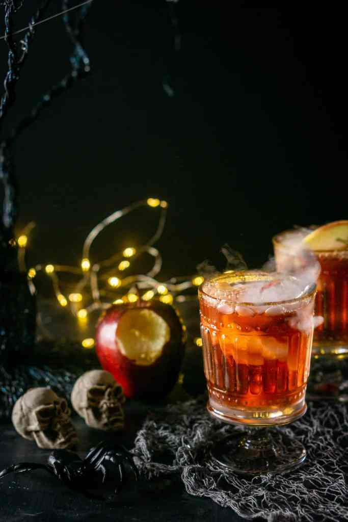 A Poisoined Orchard Cocktail with a spooky tree and bitten apple on the side.