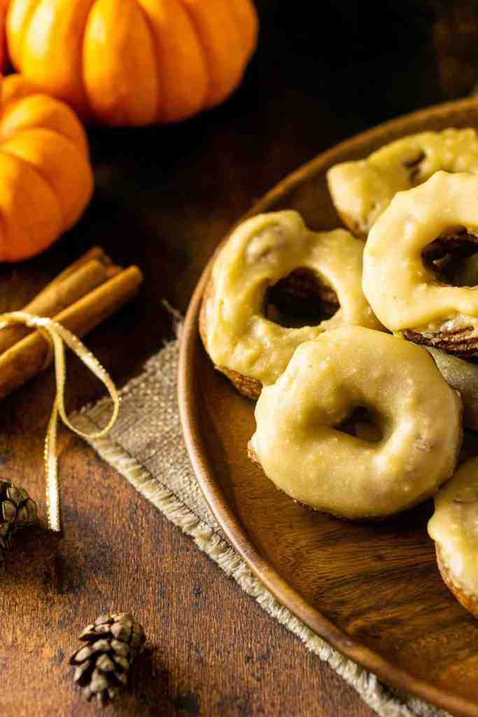 An aerial view of a plate of pumpkin crullers with cinnamon sticks and pumpkins.