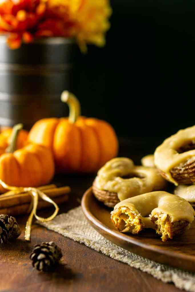 A pumpkin cruller with caramelized maple glaze sitting on a pile of other pumpkin crullers.