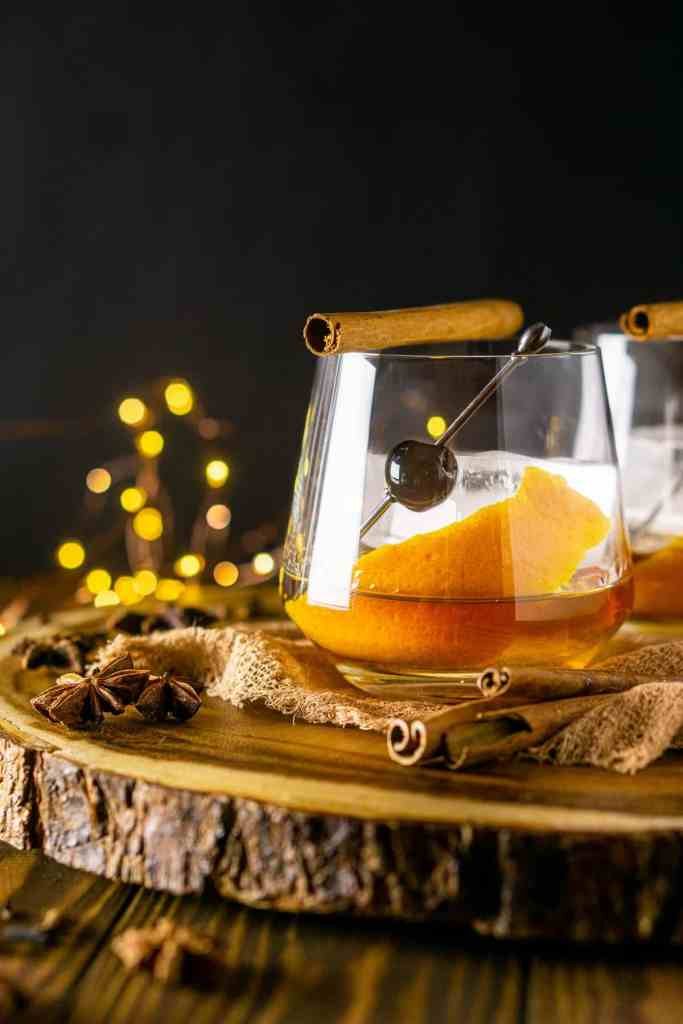A close-up shot of one chai old fashioned on dark cloth and a wooden board with a cinnamon stick on top.