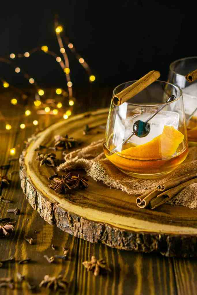A chai bourbon cocktail with a bundle of lights to the side against a black background.
