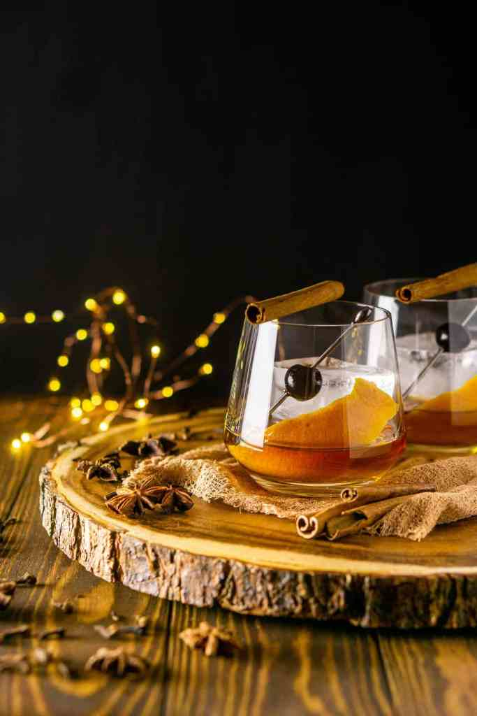 Two chai old fashioned cocktails on a wooden platter with spices on the side and lights behind them with a black background.