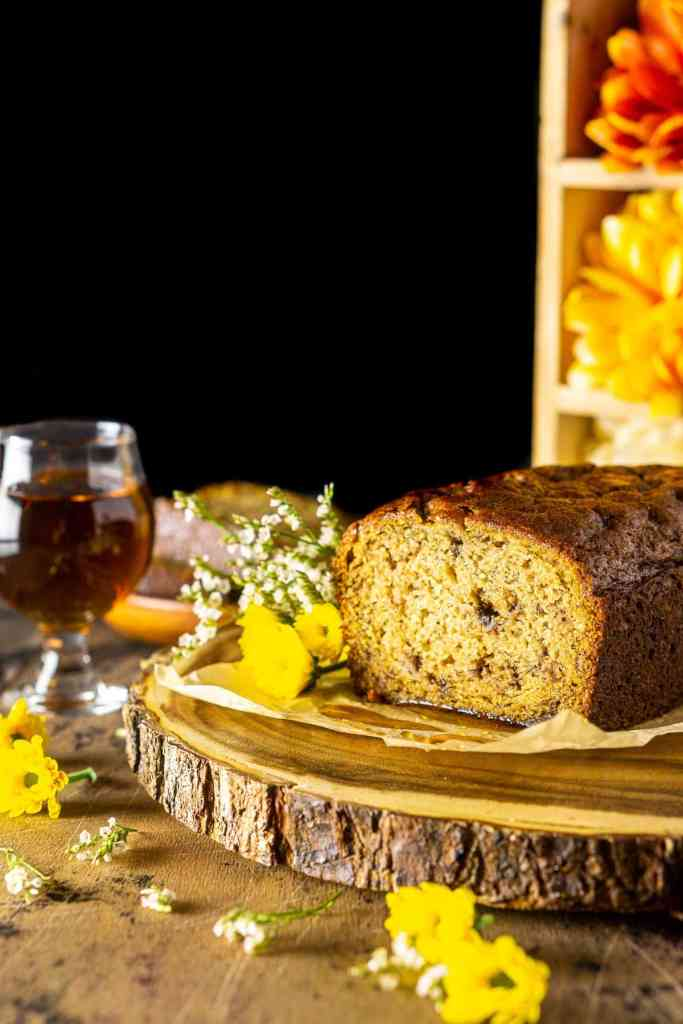 A cut loaf of maple-bourbon banana bread on a wooden platter with a glass of bourbon to the side and flowers surrounding it.