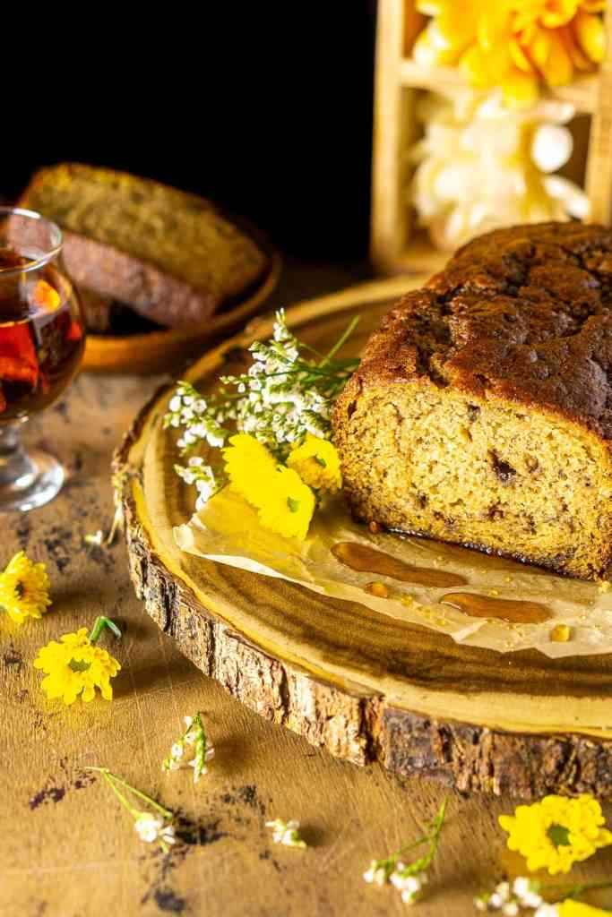 Looking down on a loaf of boozy banana bread on a wooden platter with drops of maple syrup.