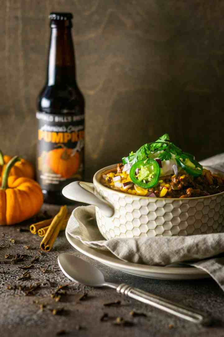 A bowl of pumpkin and chorizo chili with cloves and cinnamon sticks to the side and a pumpkin beer in the background.