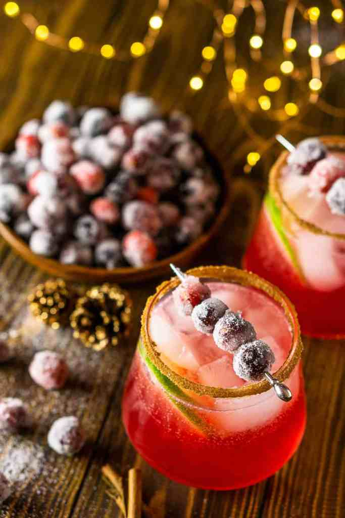 An aerial view of two sparkling cranberry-ginger margaritas with sugared cranberries behind them.