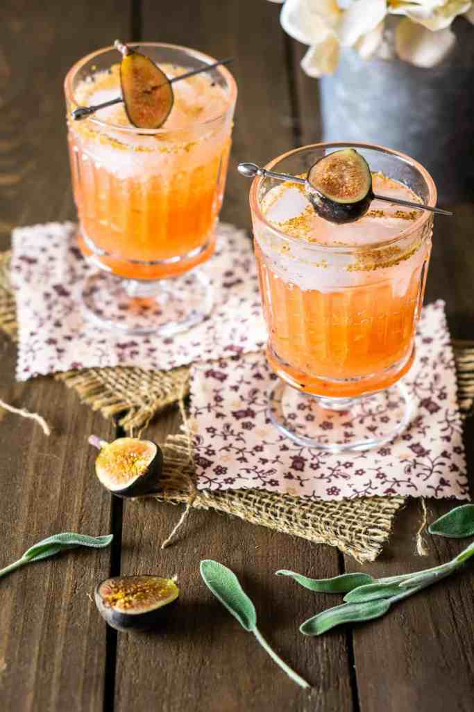 Two sage-fig cocktails on burlap and fabric with white flowers behind them.