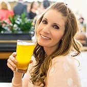A headshot of Amanda, the owner of Burrata and Bubbles, holding a beer.