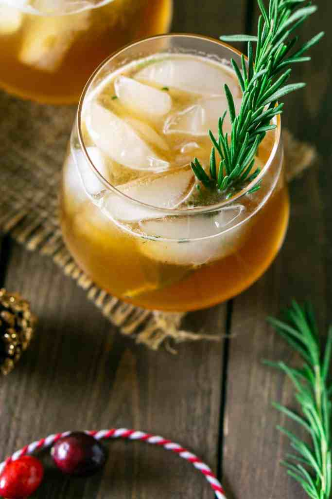 A close-up of a cranberry bourbon smash on burlap with a rosemary garnish.