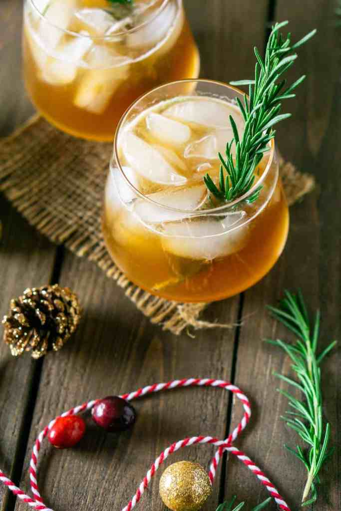 Two winter bourbon smashes with rosemary and cranberries around them.