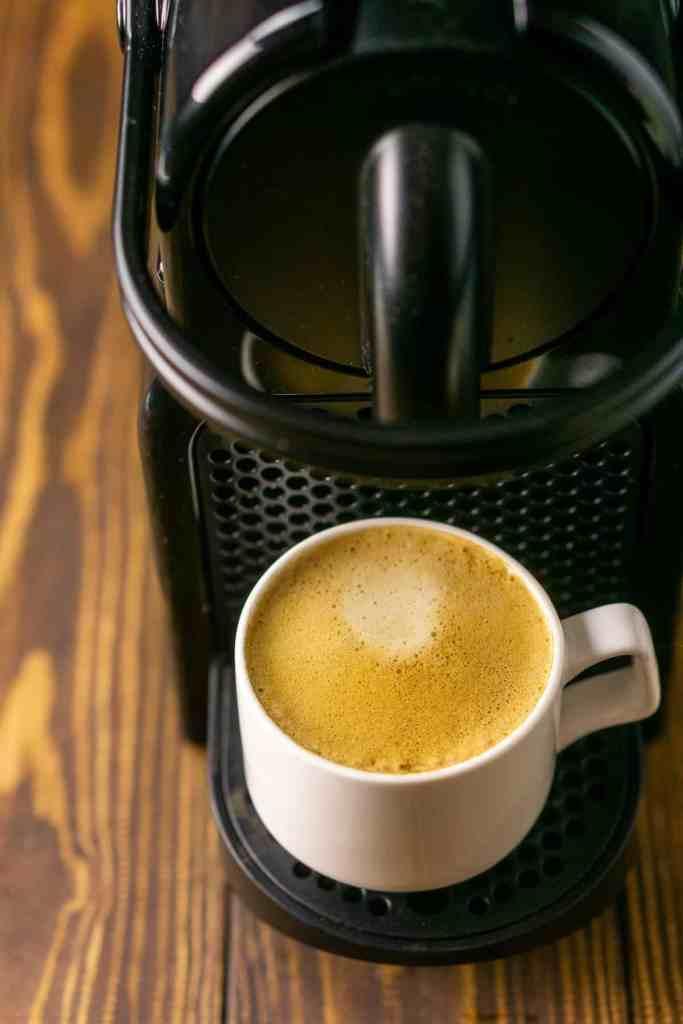 A cup of espresso sitting on a Nespresso machine.